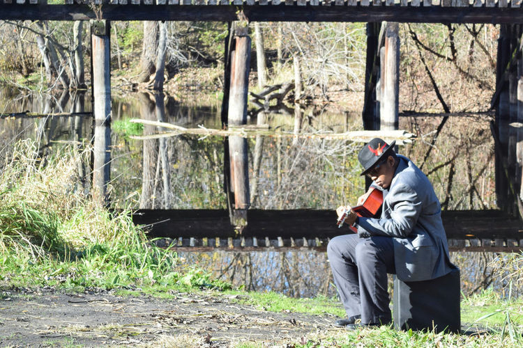 Sitting One Man Only One Person Only Men Adults Only Day Outdoors Men Adult People Musical Instrument Human Body Part Human Hand Guitar Player Man Playing A Guitar Plucking An Instrument Man By The River Nature On Your Doorstep Man With Hat Reflection Lake Guitarist Sitting Playing Beauty In Nature Naturelovers The Portraitist - 2017 EyeEm Awards