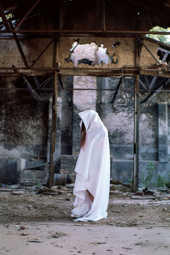 Woman Wearing White Textile Standing Against Old Abandoned Building