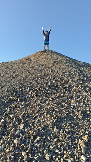 Low Angle View Of Boy Standing On Hill Against Clear Blue Sky