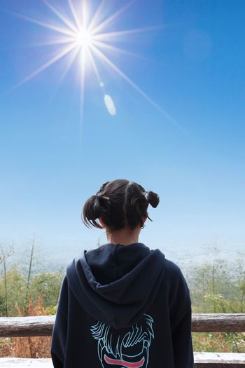 Rear view of man looking at view of sunny day