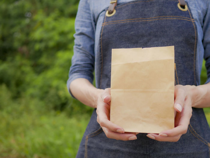 Midsection of woman holding brown paper