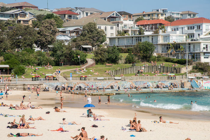 SYDNEY,NSW,AUSTRALIA-NOVEMBER 21,2016: People relaxing and enjoying water sports in the Pacific Ocean Bondi Beach in Sydney, Australia. Australia Sea Wall Apartment Architecture Beach Bondi Enjoyment Foreshore Fun Large Group Of People Leisure Activity Nature Outdoors Pacific Ocean Real People Sand Sea Sky Summer Sunbathing Sydney Travel Destinations Vacations Water Young Adult