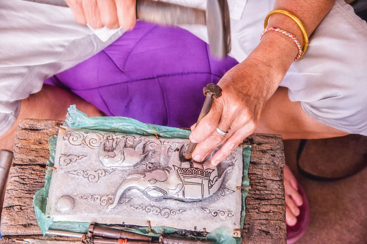 Close-up of person hands crafting sculpture at workshop
