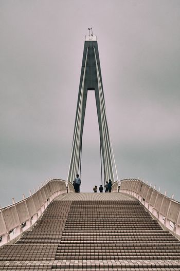 Low Angle View Of People On Bridge Against Sky