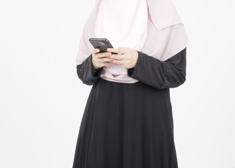 Midsection of woman holding mobile phone against white background