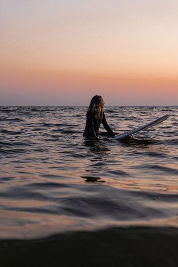 Woman with surfboard in sea against sky during sunset