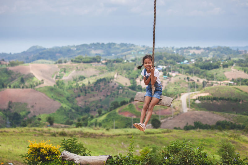 Full length of girl swinging against landscape