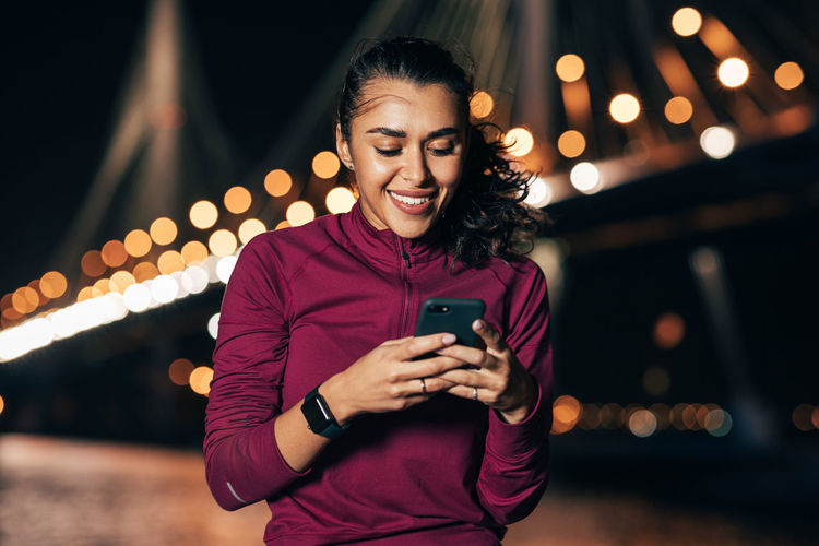 Portrait of smiling young woman using mobile phone at night