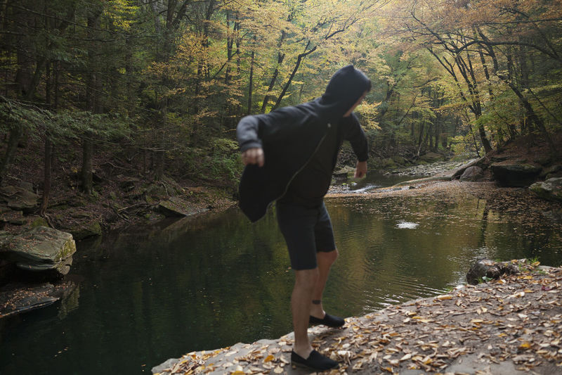 Rear view of man walking by stream in forest