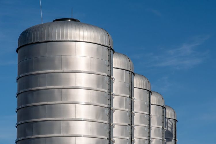 Business Finance And Industry Business Storage Production Gasoline Factory Tank Silo Sky Low Angle View Nature No People Blue Industry Day Storage Tank Metal Sunlight Clear Sky Architecture Food And Drink Storage Compartment Built Structure Cylinder Agriculture