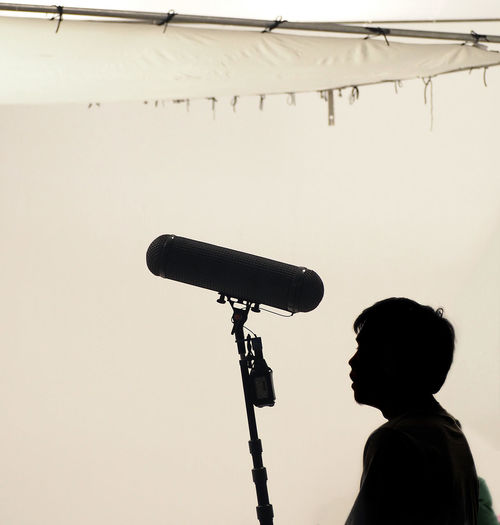 Boom Microphone hold up high by video or film production crew team man and recording sound for movie in a big studio. Boom; Microphone; Mic; White; Sound; Film; Background; Equipment; Audio; Windshield; Head; Recording; Headphones; Holding; Filming; Media; Crew; Guy; Camera; Pole; Set; Studio; Movie; Real; Production; Technology; Isolated; Broadcast; Up; Shoot; Hold; Hig Day Men One Person People Real People Recording Relaxing Sound Streetphotography Studio Technology