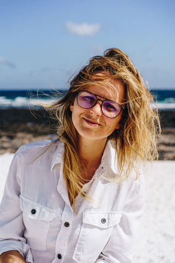 Girl Female Woman person Beautiful Smiling Happy Positive Sunny Day Beach Ocean Lifestyle Free Freedom Vacation Holidays Enjoying Enjoy Face Smile Pretty Glasses Caucasian Hair Natural Lithuanian Fuerteventura Tanned Young Attractive Model Portrait Travel Traveler Adult Shirt White Standing Blue