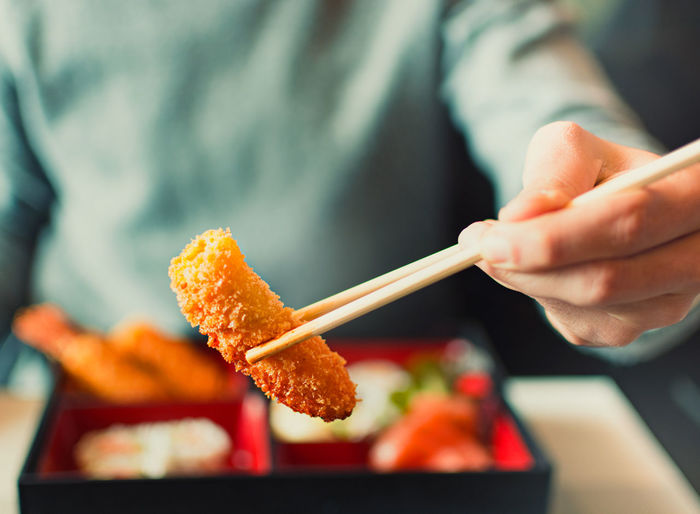 Midsection of man holding meat with chopsticks in restaurant