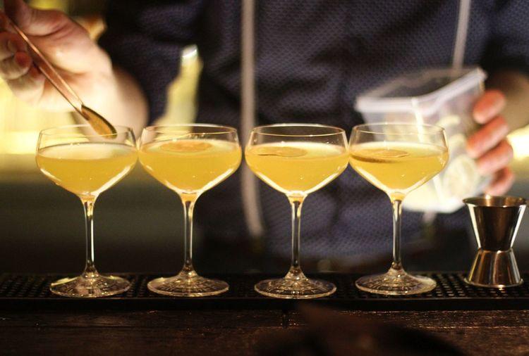 Midsection Of Bartender Making Drinks