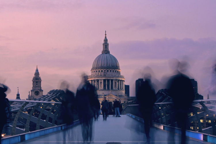 Blurred motion of people on millennium bridge leading towards st paul cathedral at dusk