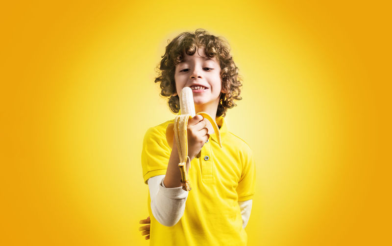 Young kid eating a banana fruit on a yellow background. Kid eating healthy food concept. Studio shot. Yellow Studio Shot One Person Colored Background Yellow Background Indoors  Portrait Holding Casual Clothing Waist Up Front View Hairstyle Mouth Open Fruit Concept Caucasian Kid Boy 7 Years Old Hair Healthy Eating Health Healthy Food And Drink Vivid Colors T Shirt Polo Shirt  Happiness Emotion Smiling Copy Space Standing Enjoyment Banana Tropical Fruit Peeled Banana Biting Colorful
