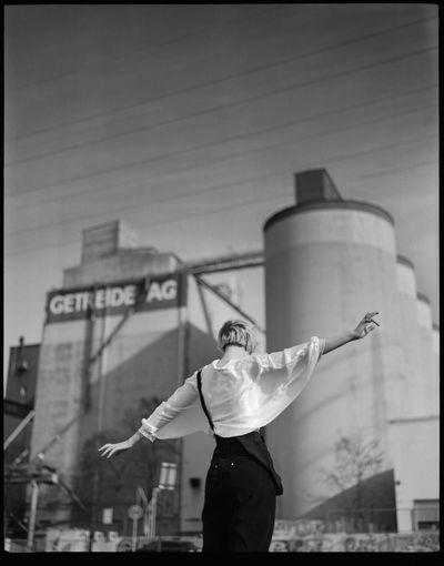 Rear view of man standing in city against sky