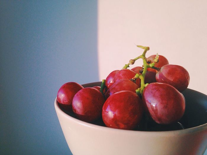 Red Grapes In Bowl Against White Wall