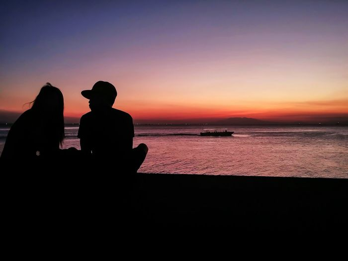 Silhouette people sitting on beach against sky during sunset