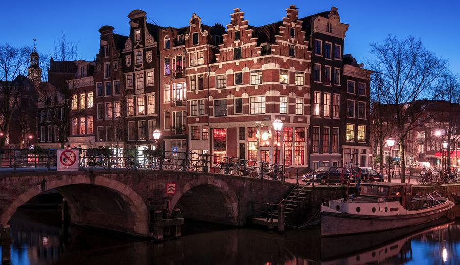 Amsterdam canal house Architecture Built Structure Building Exterior Bridge Illuminated Water City Canal Connection Nautical Vessel Arch Arch Bridge Outdoors Amsterdam Amsterdam Canals Architecture Canal Houses Capital Cities  Historical Building Blue Hour Evening No People