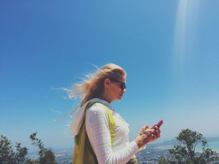 Side view of woman using mobile phone against blue sky