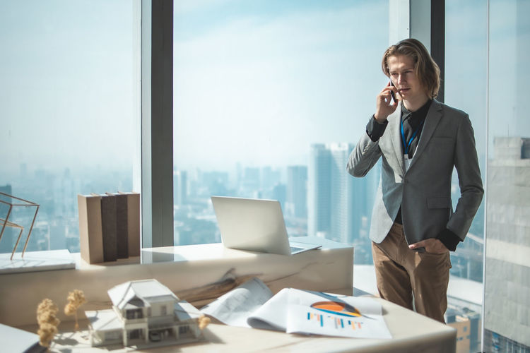 Businessman talking over mobile phone while standing by window
