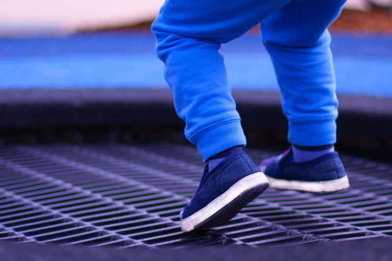 A boy on the playground jumping on a trampoline. A view of legs hovering in the air. Fun Funny Joyful Jump Activity Blue Boy Child Close-up Day Joy Kid Legs Motion One Person Outdoors Pants Playground Shoe Trampoline