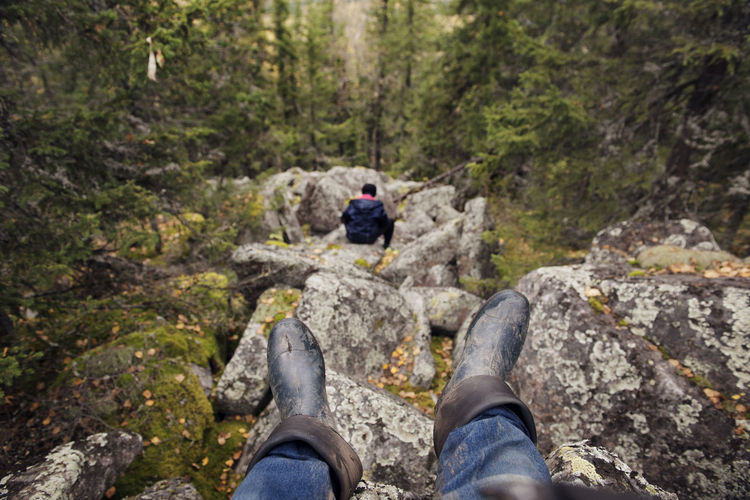 Low section of man on rock in forest