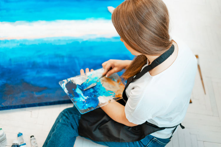 High angle view of woman painting on canvas