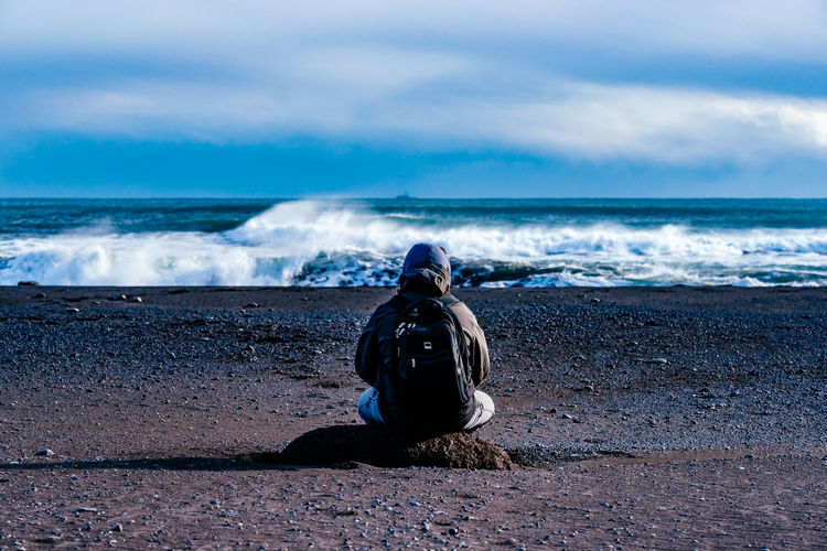 Rear View Of Backpacker Sitting At Beach Against Cloudy Sky