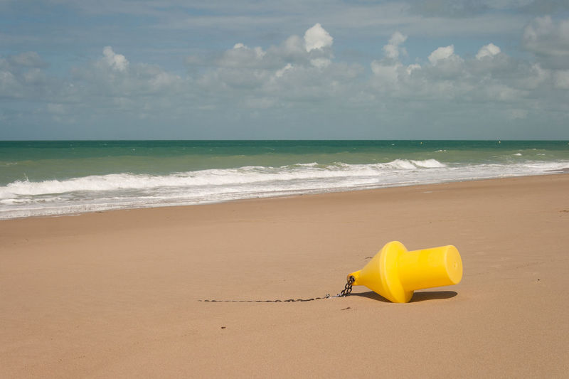 Yellow umbrella on beach against sky