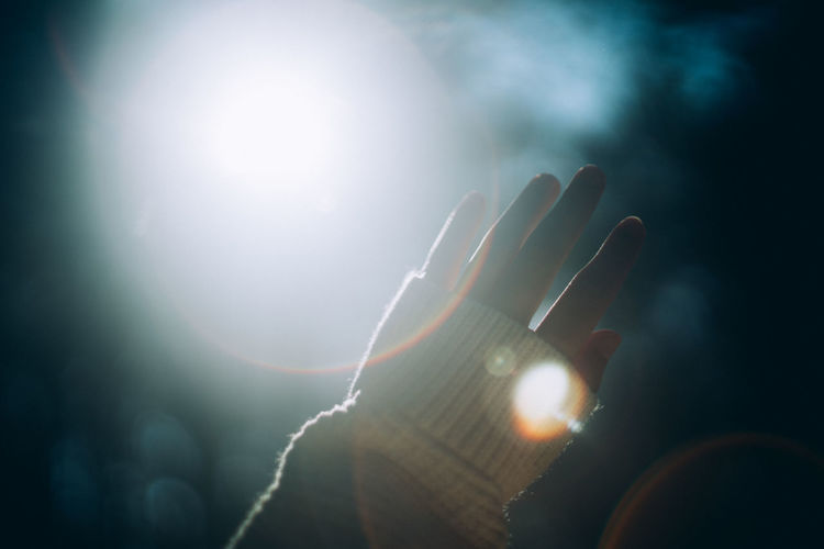 Close-up of hand against sky during sunny day