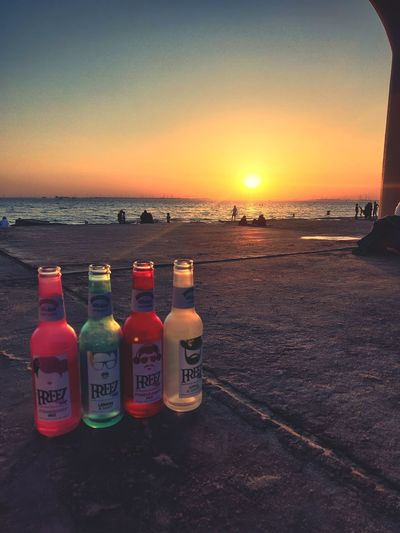 View of bottles on beach against sky during sunset