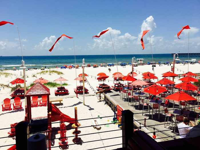 Red parasols at beach against sky