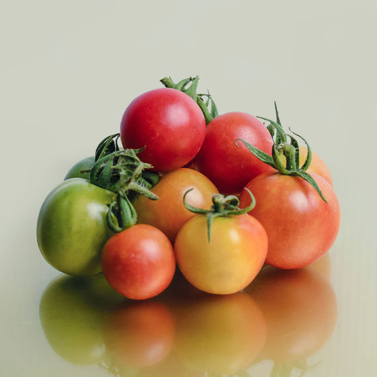 Close-up of tomatoes on table against white background