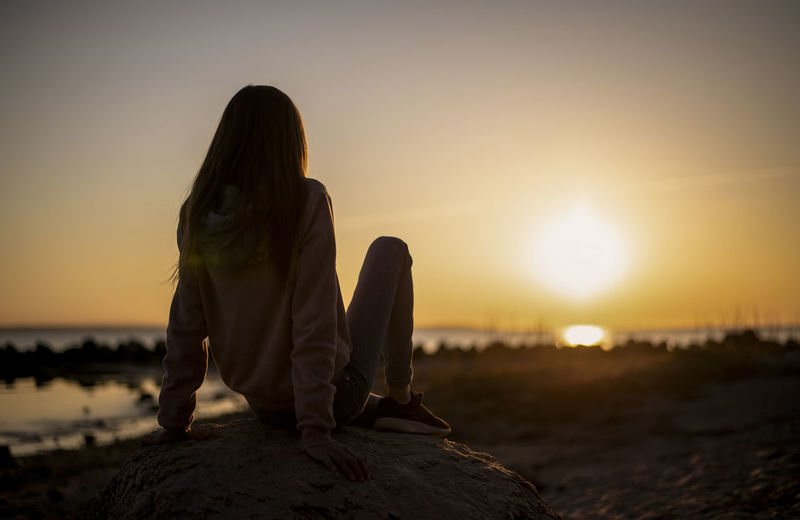Rear view of girl sitting at beach during sunset