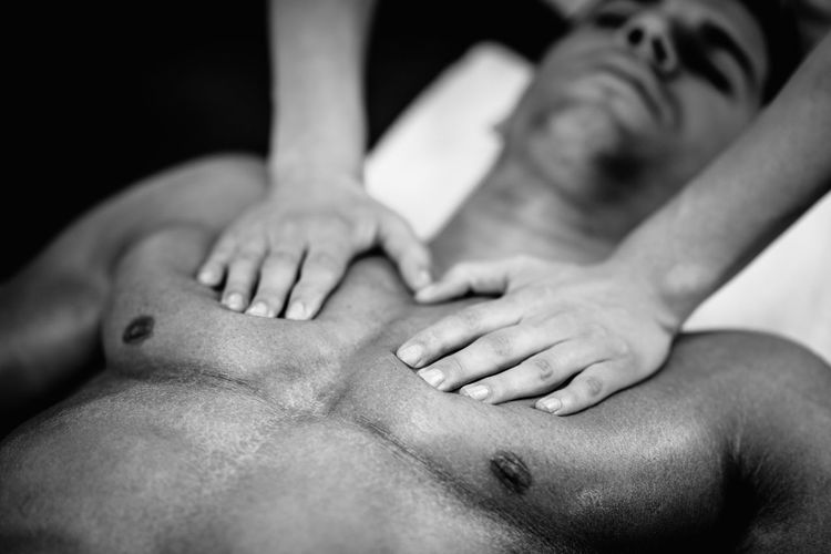Woman Massaging Man Lying On Bed