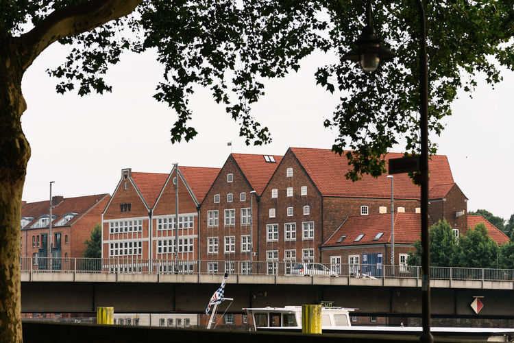 Houses by river and buildings against sky
