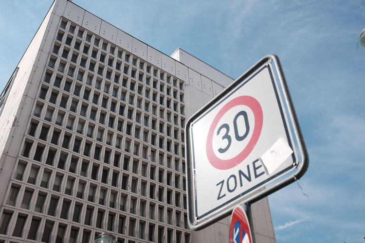 Low angle view of speed limit sign against building in city