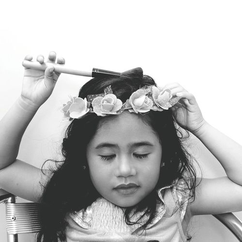 Girl with closed eyes wearing flowers holding brush while sitting on chair against wall