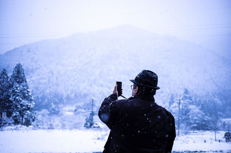 Rear View Of Man Photographing Snowfall