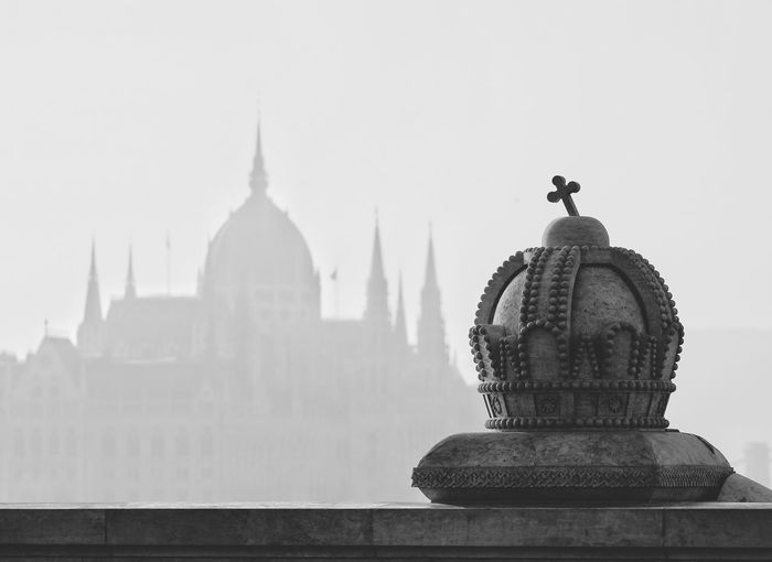 Crown Shaped Sculpture On Retaining Wall With Hungarian Parliament Building In Background