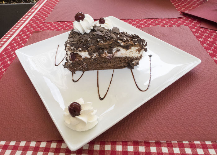 Slice of black forest cake on a white plate on a table Black Forest Cake Cake Food SLICE Slice Of Cake Plate Plate Of Food Table Dessert Indulgence Chocolate Unhealthy Eating High Angle View Chocolate Cake Food And Drink