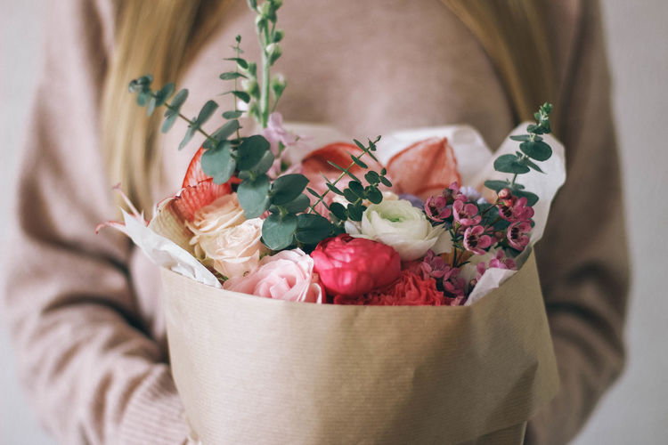 Midsection Of Woman With Bouquet Of Flowers