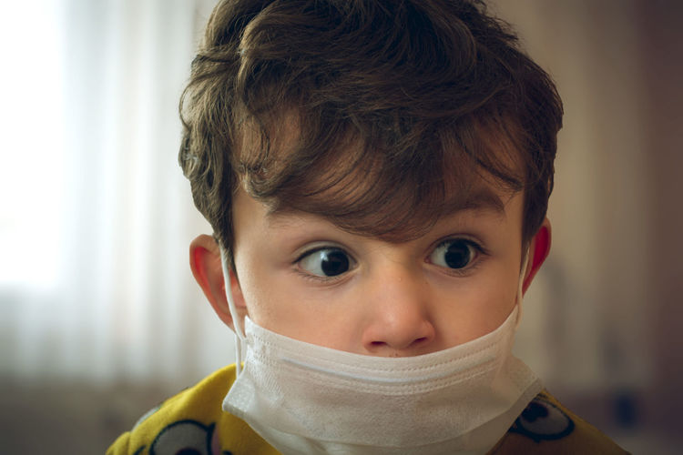 Close-up of cute boy wearing mask at home