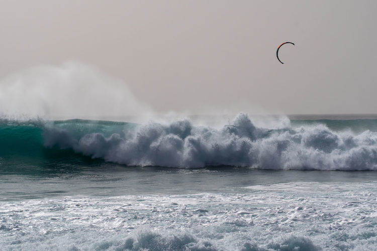 Kite sailing  and waves splashing in sea against sky