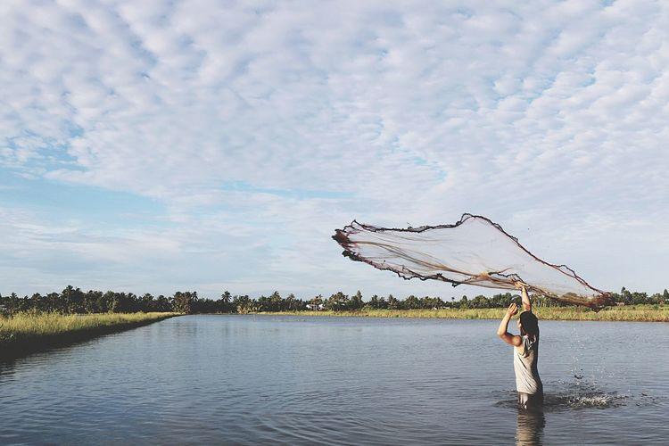 Fisherman Throwing Net In Lake Against Sky