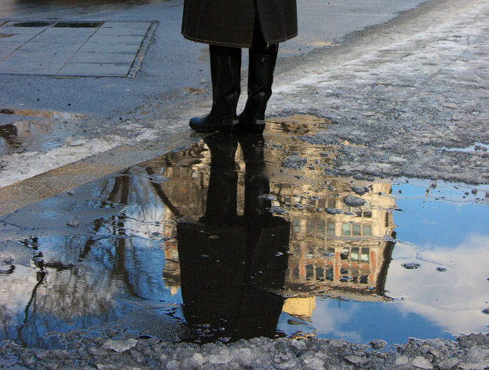 Low section of person reflecting in puddle on street