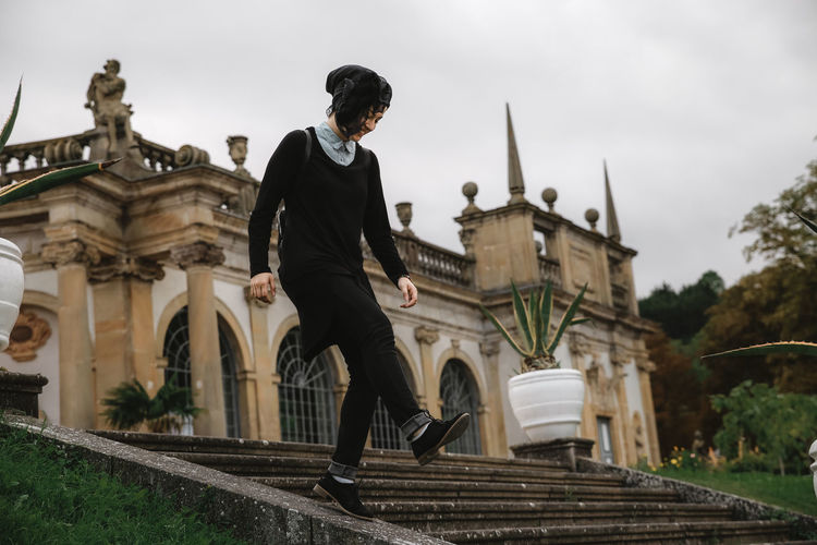 Woman walking by steps against building