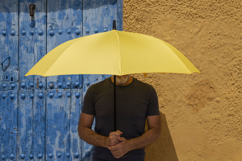 Portrait of adult man with yellow umbrella standing against blue door and yellow wall in summer